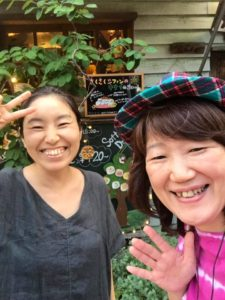 カフェの前で記念撮影する女性2人
