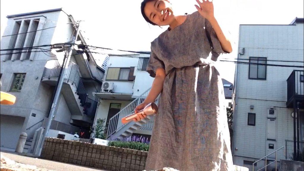 民家の並ぶ住宅街で歌う女性