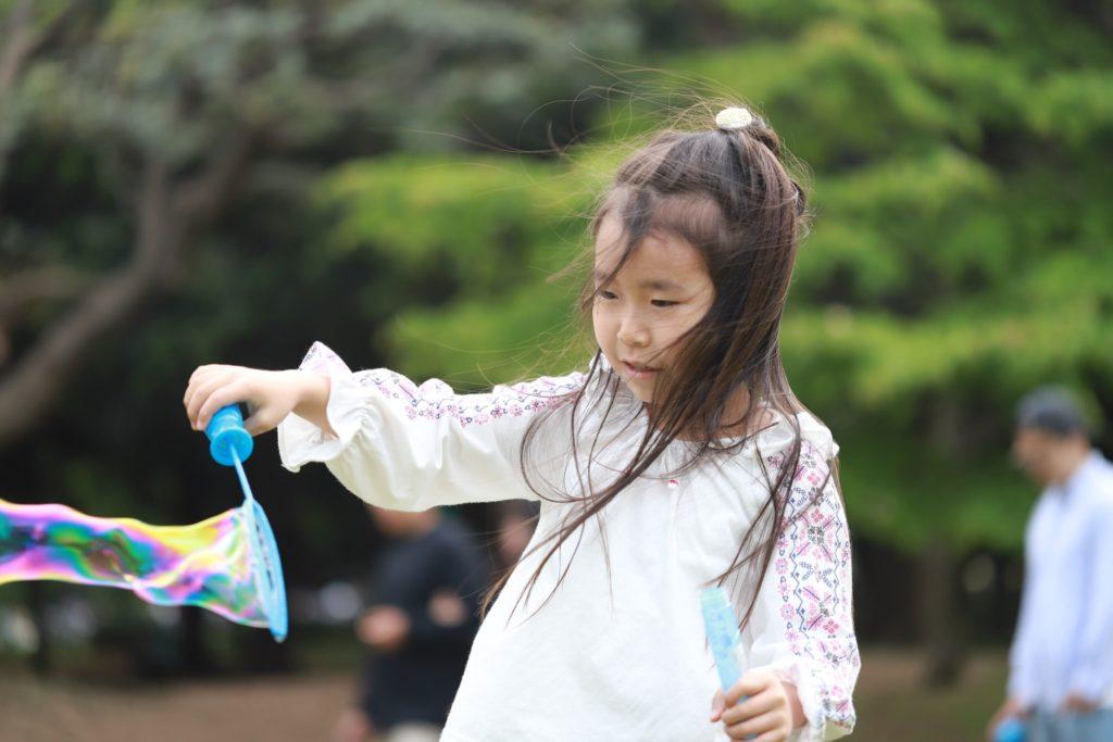 公園でシャボン玉を作って遊ぶ少女