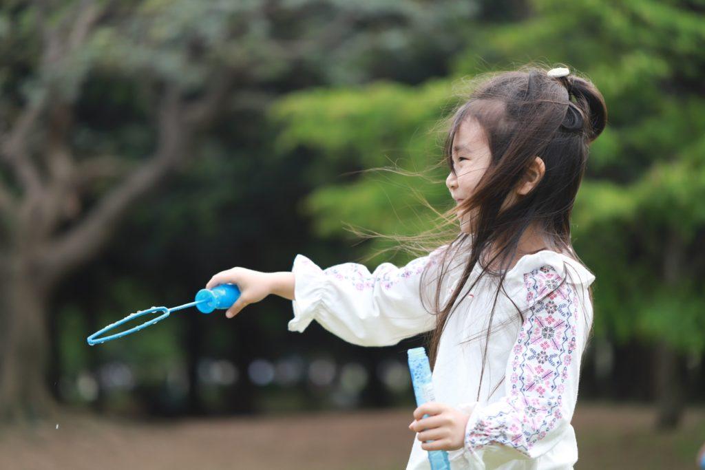 シャボン玉を飛ばして遊ぶ少女