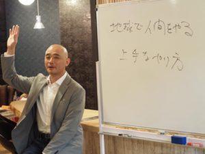ホワイトボードの前で講演をする男性