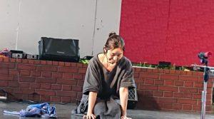 ひとり演劇のスタート前に舞台上で床に手をついている女性