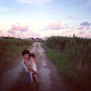島での夕日ときび畑のなかで赤ちゃんを抱っこする少女