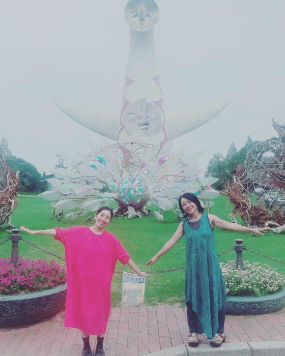 太陽の塔をバックに両手を広げて写っている女性2人