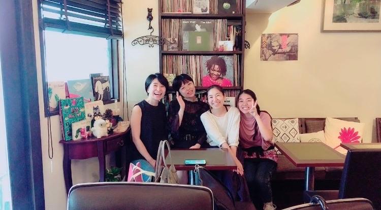 カフェで並んで記念撮影をする女性4人
