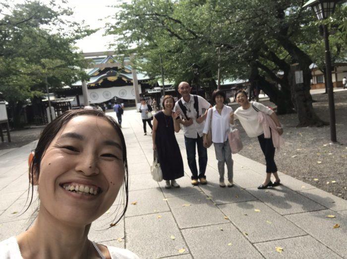靖国神社の本殿の前で記念撮影をする男女のグループ