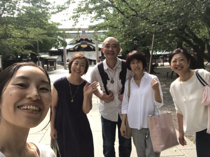 靖国神社の本殿前に記念撮影をする男女のグループ