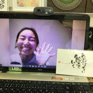 オンラインセッション後に満面の笑みで微笑む女性が写っているパソコンの画面