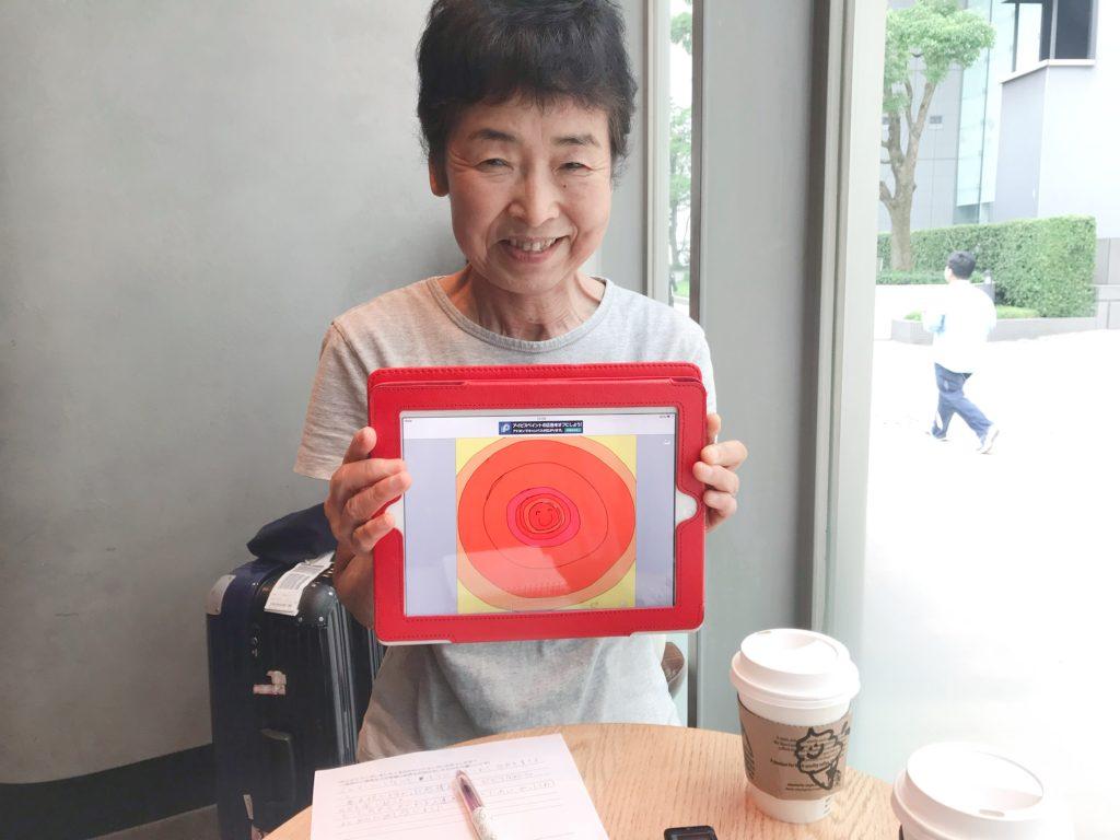カフェにて楽しそうに魂のイラスト画面を持って微笑む女性