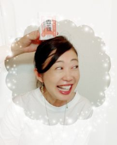 頭の上に雪の魂という富士山のお土産を乗せられて笑う女性
