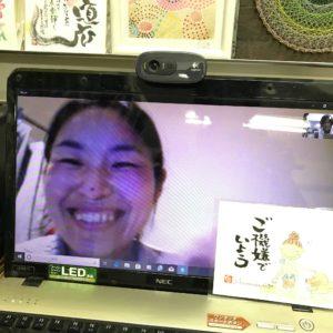 オンラインセッションでパソコンごしに満面の笑みで微笑む女性