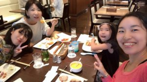 ホテルランチビュッフェを囲んで楽しそうに笑っている家族の写真