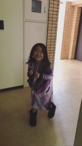 ニットのコートの襟部分を握りしめて満面の笑みで見つめてくる少女