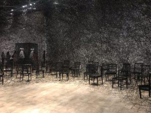 塩田千春展魂がふるえるの展示の中で真っ黒に焦げた椅子が黒い糸で張り巡らされた展示