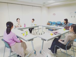 会議室でテーブルを囲んで雑談する女性たち
