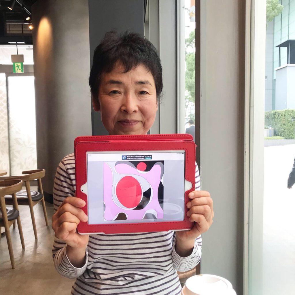 カフェセッションが終わりご自身の魂のイメージイラストを持って微笑む女性