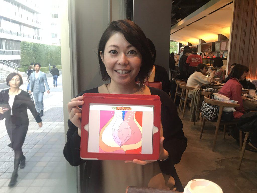 カフェの中でカウンセリングが終わってから魂のイラストを持って微笑む女性