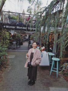 代々木にある代々木ビレッジにてカフェが並ぶ前で記念写真を撮る女性