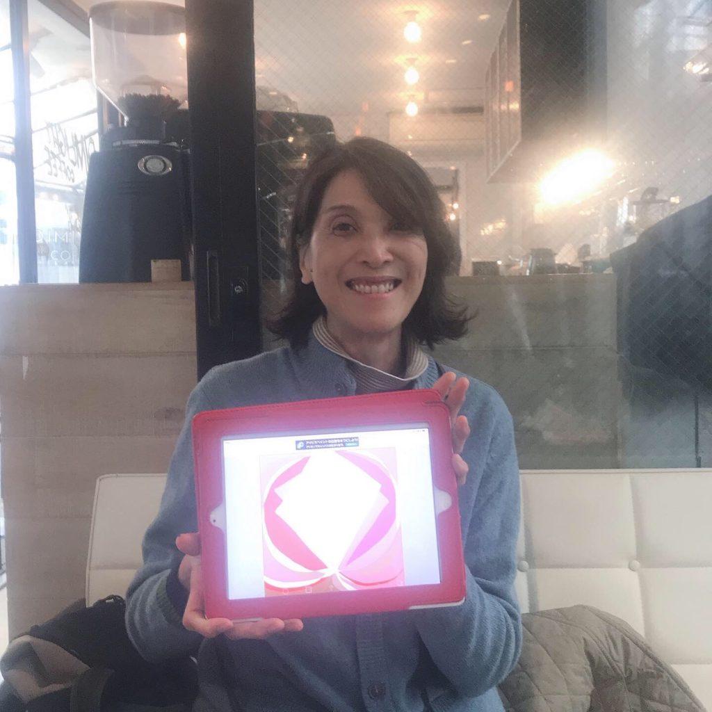 代々木のカフェのソファ席で子宮のイラストを持ちながら微笑む女性