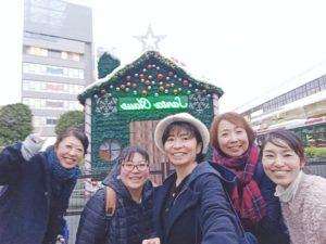 吉祥寺の駅前のサンタクロースのお家のオブジェ前で記念写真を撮る女性たち