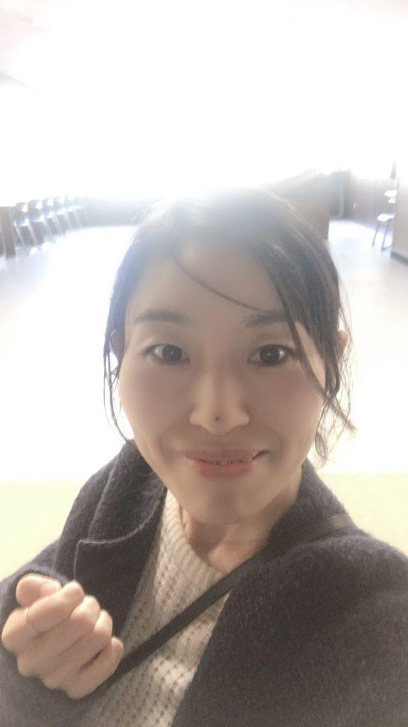娘の中学校の廊下で写真を撮って笑っている女性