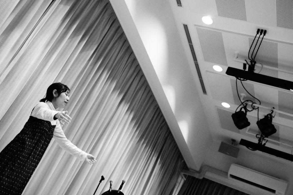 舞台の上で1人芝居をする女性が両手を広げて台詞を言っている白黒の写真