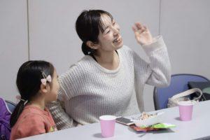 大きく手を振って楽しげに笑っている女性とその娘が並んで座っている様子