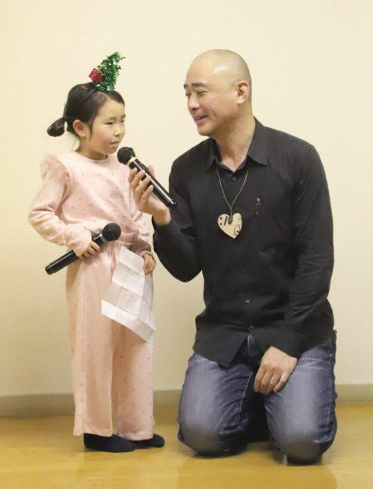 舞台の上でインタビューを受ける幼児と司会の男性