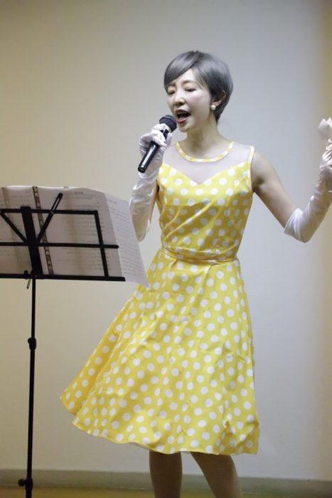 黄色い水玉のドレスを着てマイクで踊りながら歌う女性