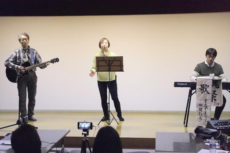 父親と母親と息子で組まれたユニットでギターとピアノの伴奏で歌うシーン