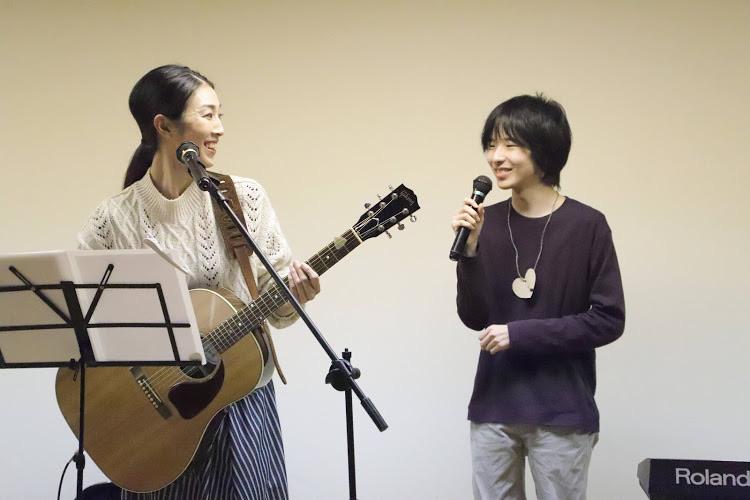 司会者の中学生の男子とギターを弾き語りした女性が笑い合う写真