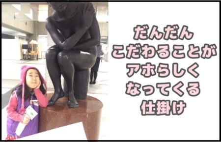 役場の銅像オブジェの前で縦ヒジをつき変顔をしている幼児